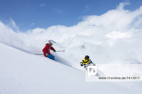 Skifahrer und Snowboarder auf verschneiter Piste
