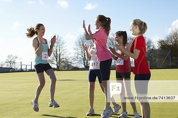 Runners cheering together in field