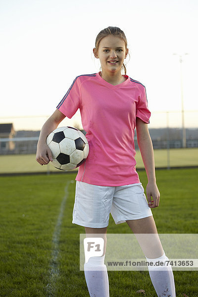 Football player holding ball in field