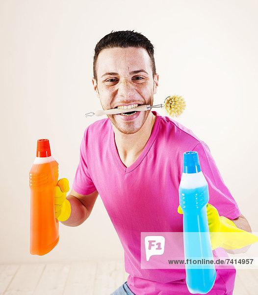 Fröhlicher junger Mann mit Putzmitteln und Bürste Fröhlicher junger Mann mit Putzmitteln und Bürste