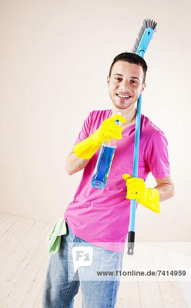 Fröhlicher junger Mann beim Hausputz Fröhlicher junger Mann beim Hausputz