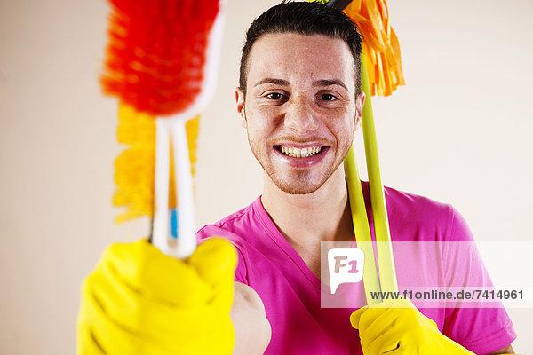 Fröhlicher junger Mann beim Hausputz  Portrait Fröhlicher junger Mann beim Hausputz, Portrait