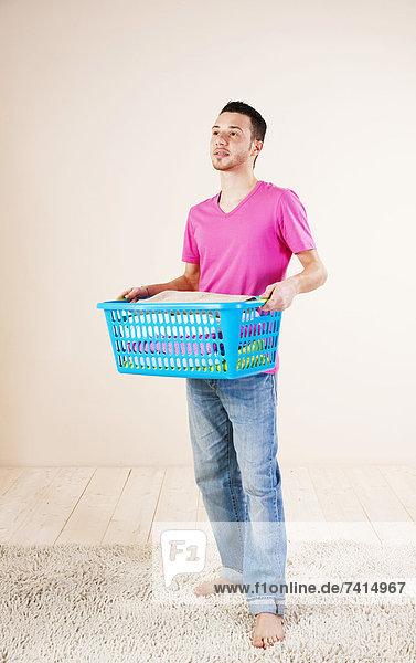 Junger Mann mit Wäschekorb Junger Mann mit Wäschekorb