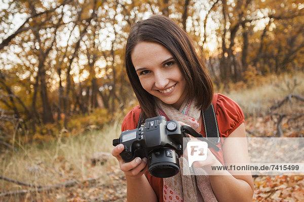 liegend liegen liegt liegendes liegender liegende daliegen junge Frau junge Frauen Portrait lächeln Laub