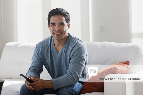 Portrait of smiling mid adult man sitting on sofa