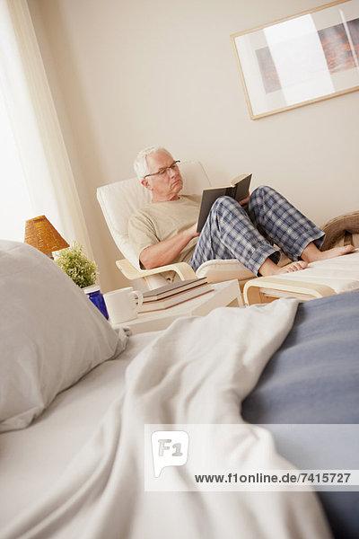 sitzend  Senior  Senioren  Mann  Buch  Schlafzimmer  Taschenbuch  vorlesen