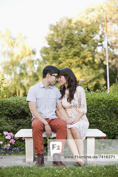 Couple sitting on bench in park