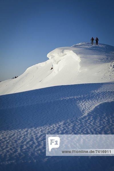hoch  oben  Berg  Mensch  zwei Personen  Menschen  Silhouette  Beleuchtung  Licht  Sonnenaufgang  lila  Skisport  unbewohnte  entlegene Gegend  2