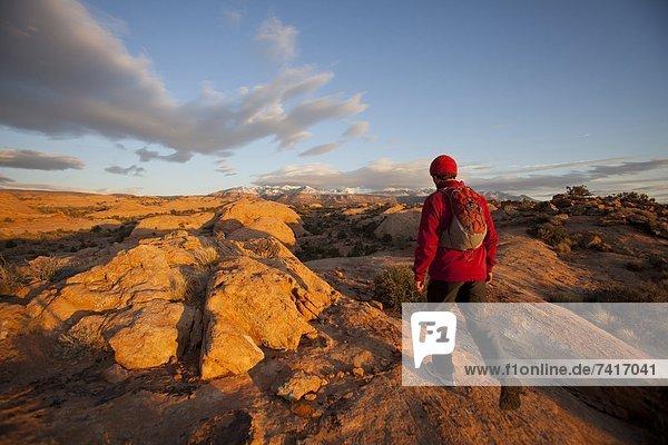 Young man hiking on slickrock near Moab  Utah.