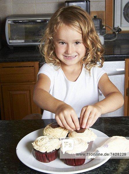 Kleines Mädchen dekoriert Cupcakes in der Küche