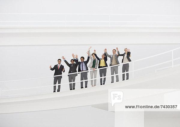 Porträt von jubelnden Geschäftsleuten auf erhöhtem Steg