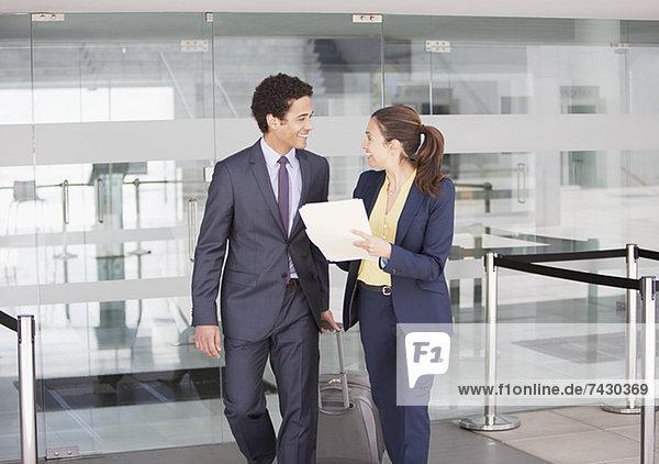 Lächelnder Geschäftsmann und Geschäftsfrau mit Akte am Flughafen
