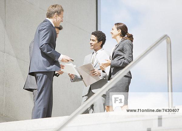 Geschäftsleute mit Papierkram am oberen Ende der Treppe