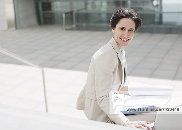 Portrait of smiling businesswoman with laptop and paperwork outside building