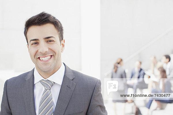 Porträt eines lächelnden Mannes mit Mitarbeitern im Hintergrund
