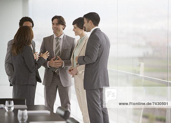 Geschäftsleute sprechen am Fenster des Konferenzraumes