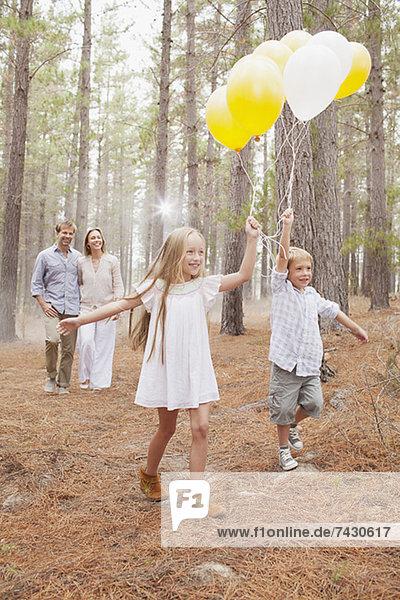 Glückliche Familie mit Ballons im Wald