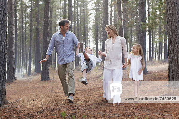 Happy family holding hands and walking in woods