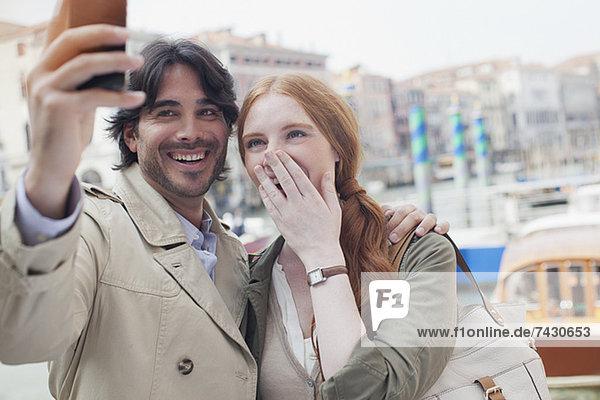 Lachendes Paar beim Selbstporträt mit Fotohandy in Venedig