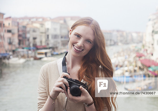 Portrait of smiling woman holding digital camera at waterfront in Venice
