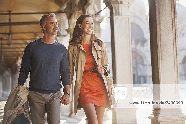 Lächelndes Paar hält sich an den Händen und geht in Venedig den Flur entlang.