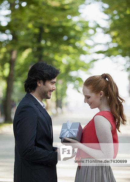 Mann schenkt Frau im Park