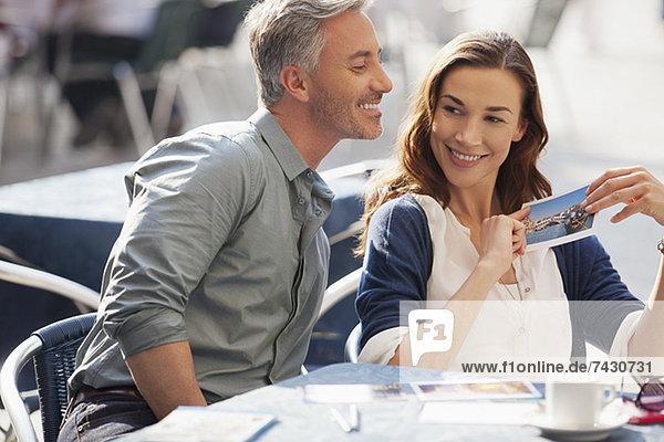 Lächelndes Paar mit Postkarte im Straßencafé