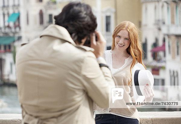 Mann fotografiert lächelnde Frau mit Hut in Venedig