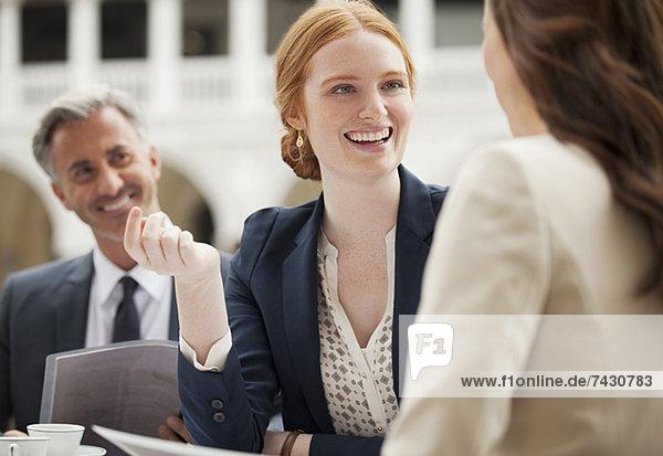 Lächelnde Geschäftsleute treffen sich im Straßencafé