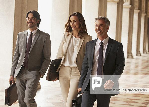Lächelnde Geschäftsleute gehen den Flur entlang