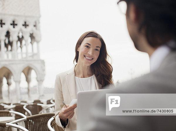 Lächelnde Geschäftsfrau trifft sich mit Geschäftsmann im Straßencafé