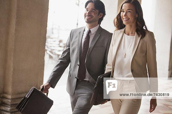 Lächelnder Geschäftsmann und Geschäftsfrau beim Gehen