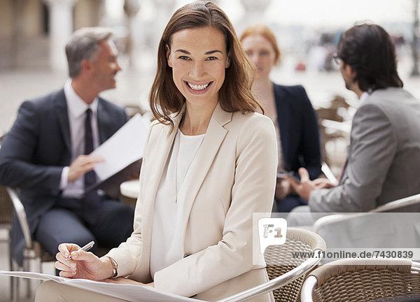 Porträt einer lächelnden Geschäftsfrau  die im Straßencafé arbeitet.