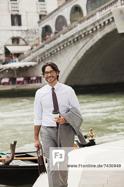 Portrait of smiling businessman with coffee walking along canal in Venice