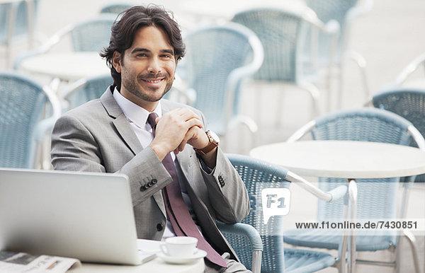 Porträt eines lächelnden Geschäftsmannes mit Laptop und Espresso im Straßencafé