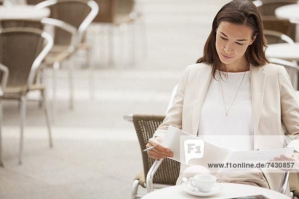 Seriöse Geschäftsfrau liest Papierkram im Bürgersteigcafé