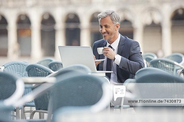 Lächelnder Geschäftsmann trinkt Kaffee und benutzt Laptop im Straßencafé