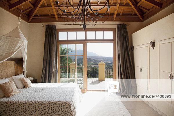 Bett mit Vordach und Fenstertüren zum Balkon im Schlafzimmer