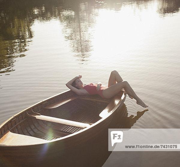 Gelassene Frau beim Sonnenbaden im Boot auf dem See