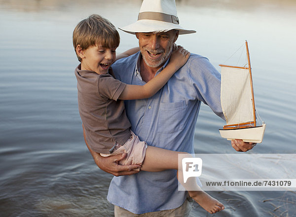 Lächelnder Großvater und Enkel mit Spielzeug-Segelboot  das im See watet