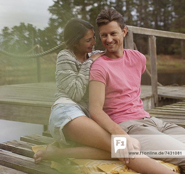 Lächelndes Paar sitzt auf dem Dock über dem See.