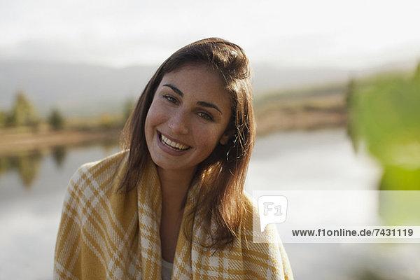 Porträt einer lächelnden Frau am Seeufer