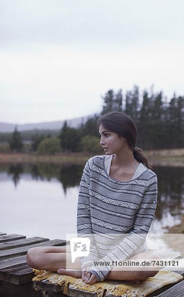 Nachdenkliche Frau auf dem Dock am See sitzend