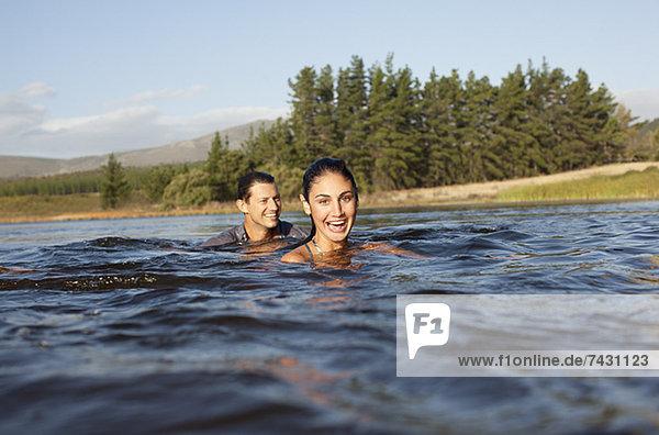 Porträt eines lächelnden Paares beim Schwimmen im See