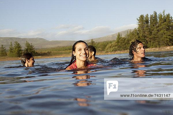 Lächelnde Freunde schwimmen im See
