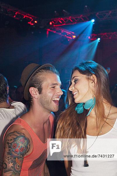 Lächelndes Paar tanzt im Nachtclub