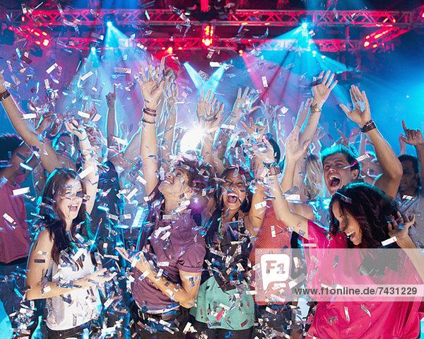 Konfetti fallen über die begeisterte Menge auf der Tanzfläche des Nachtclubs