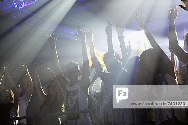 Menschenmenge mit erhobenen Armen hinter dem Geländer beim Konzert