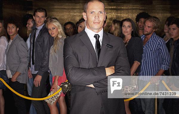 Porträt eines ernsthaften Türstehers mit gekreuzten Armen vor der Schlange im Nachtclub.