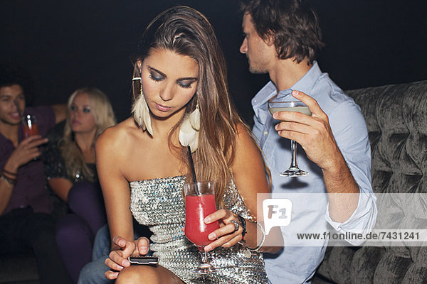 Frau mit Cocktail-Check-Handy im Nachtclub